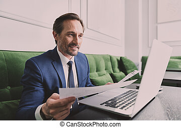 Successful businessman reading documents while using...