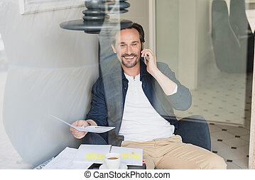 Happy businessman talking on smartphone in cafeteria - Waist...