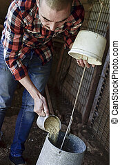 farmer man filling a feeder in a henhouse - closeup of a...