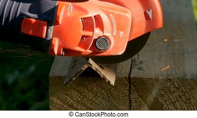man sawing metal by grinder close-up - man sawing metal by...