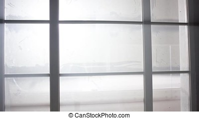 Bright white light outside the window. Spotlight outside the window. Half open window with view to the outside half on gray storm and half on clouds in blue sky with sun
