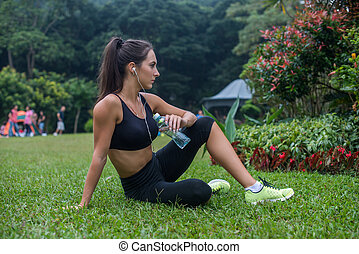 Thoughtful fitness girl sitting on grass in park resting...