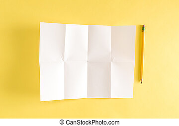 Pencil and blank sheet of folded paper