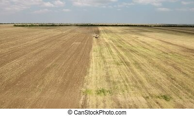 Aerial shot of an agricultural field and a big tractor...