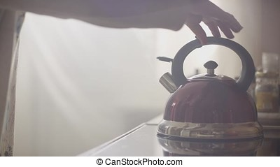 Girl put blue kettle on a kitchen gas stove. Stovetop...