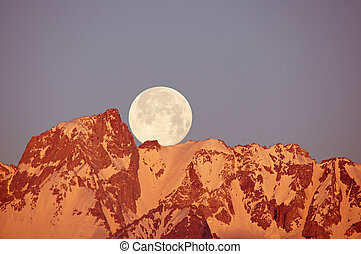 Moon Setting Over Mountain - a full moon setting over Mount...