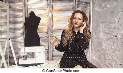 Girl tailor talking on the phone in the Studio