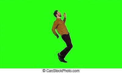 Guy is dancing energetically, he is having fun. Green...