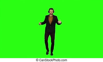 Businessman in headphones, whirl in dance. Green screen. Slow motion