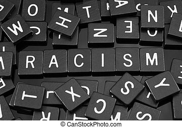 """Black letter tiles spelling the word """"racism"""" on a..."""