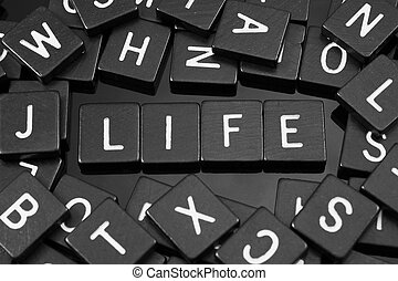 """Black letter tiles spelling the word """"life"""" on a reflective..."""
