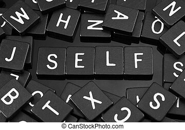 "Black letter tiles spelling the word ""self"" on a reflective..."