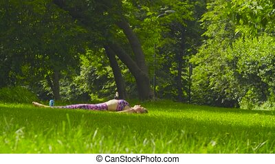 Young woman doing yoga exercises in the park. Halasana....
