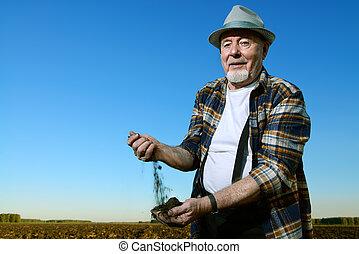 a farmer holds - An elderly farmer holds a handful of...
