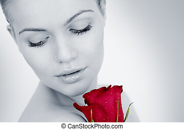 Thoughtful girl with a red rose on a gray background