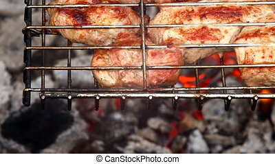 Cooking meat over an open fire. Smoke and flames from...