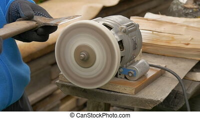 The man is sharpening an ax. - Work on a sharpening machine....