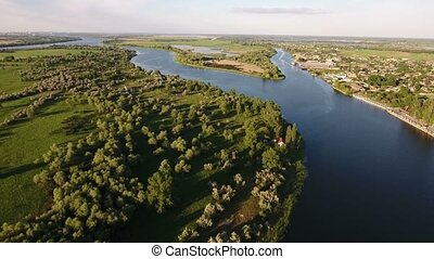 Aerial shot of the Dnipro riverbanks with a modern quaya and greenary at sunset