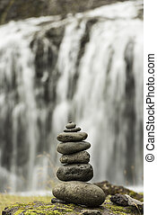 Stack of pebbles and waterfall