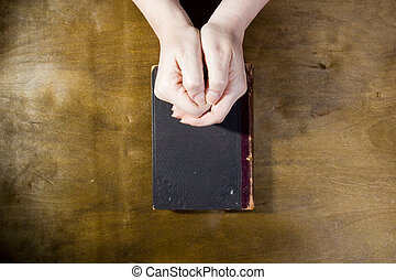 Female hands in prayer with a book on a wooden background