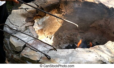 Ignition of a fire in a stone hearth with a long match -...