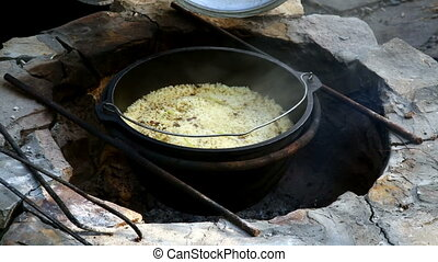 Uzbek national dish pilaf in a large cast-iron cauldron on...