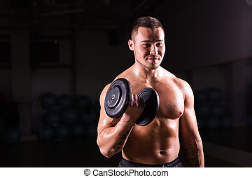 Athletic shirtless young male fitness model holds the dumbbells.