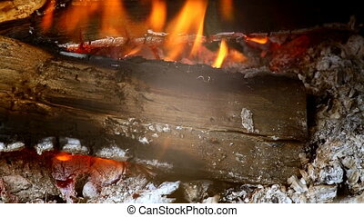 Close view at a glowing charcoal and flame in the barbecue...