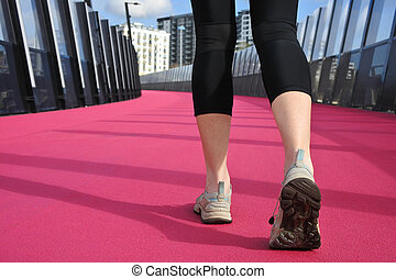 Womans legs walking on a bright pink road - Low angle of a...