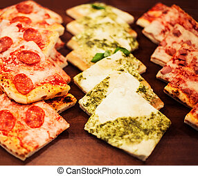 Pizza pieces to go on a stall in pizzeria, may use as...