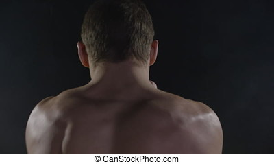 Punching. Muscular man boxing on black background. Boxer practicing shadow boxing