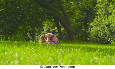 Young woman sitting on the grass in the park
