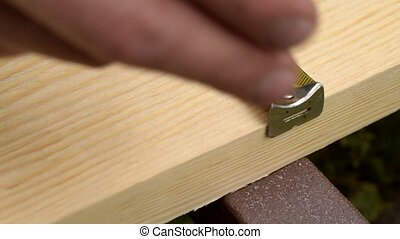 Marking wood with pencil and measuring tape and drilling -...