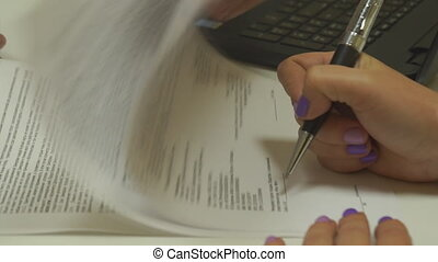 female hand signing a contract paper