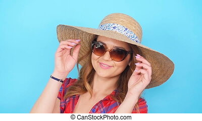 Young woman in sunglasses and hat smiling