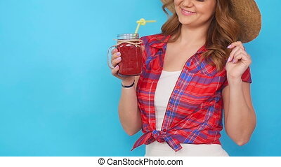 Beautiful young woman holding a red smoothie glass in hand