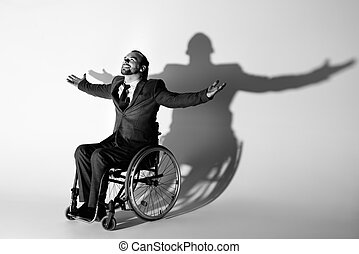cheerful businessman in suit sitting in wheelchair gesturing with shadow on white wall, black and white