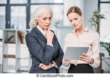 Two serious businesswomen in formal wear using digital...