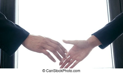 Slow motion of hand shaking between a businessman and businesswoman