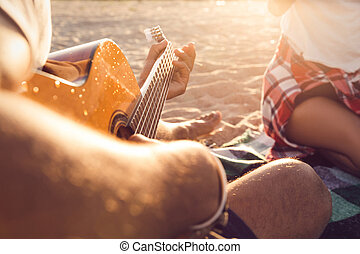 Cropped image of a guy playing guitar for his friends at the...