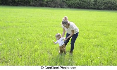 Mother with little son doing first steps on green meadow -...