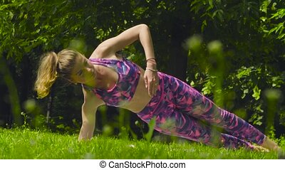 Young woman doing yoga exercises in the park. Chaturanga...
