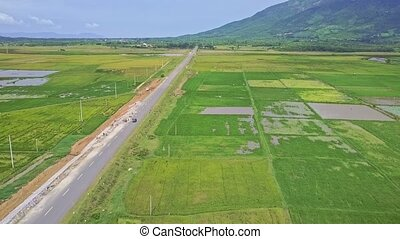Flycam Shows Road with Driving Car among Rice Fields -...