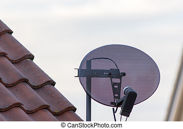 Satellite tv dish on residential home property roof. Metal...