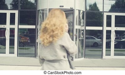 A young woman walking into the shop door