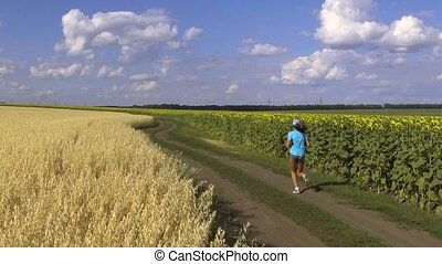 woman running in the blooming sunflowers field. - young...