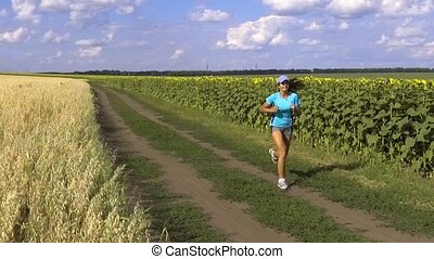 woman running in the blooming sunflowers field. slow motion