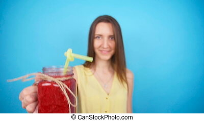Young woman holding a glass of red smoothies