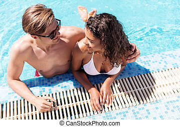 Jolly youthful man and woman enjoying their rest in water