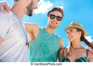 Cheerful attractive youthful friends having rest outdoor